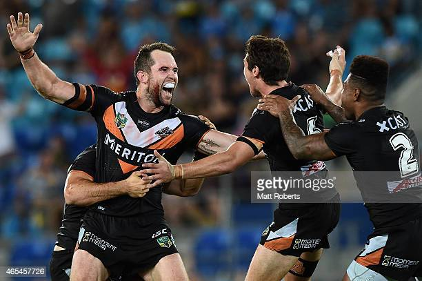 Pat Richards of the Tigers celebrates kicking a field goal with team mates during the round one NRL match between the Gold Coast Titans and the Wests...