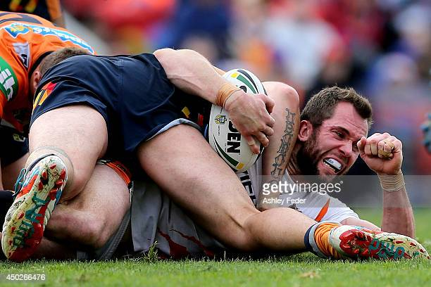 Pat Richards of the Tigers is tackled during the round 13 NRL match between the Newcastle Knights and the Wests Tigers at Hunter Stadium on June 8...