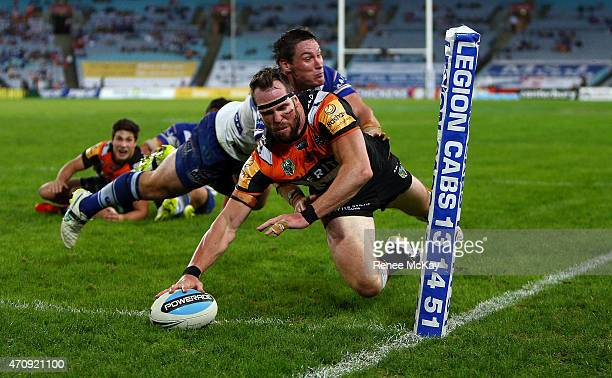 Pat Richards of the Tigers scores a try in the tackle of Bulldogs player Josh Jackson during the round eight NRL match between the Canterbury...