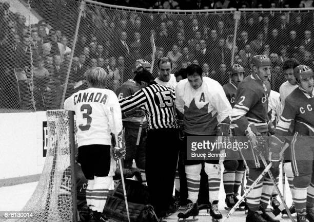 Pat Stapleton and Frank Mahovlich of Canada stand in the crease as goalie Vladislav Tretiak of the Soviet Union was knocked into his net during a...