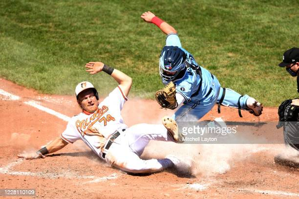Pat Valaika of the Baltimore Orioles is tagged out by Reese McGuire of the Toronto Blue Jays trying to tag up on a hit by Chance Sisco in the forth...