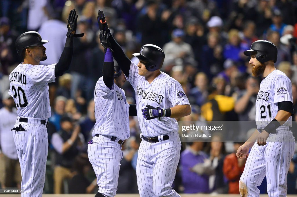 Pat Valaika #4 of the Colorado Rockies celebrates with Ian Desmond #20, Alexi Amarista #2, and Jonathan Lucroy #21 after all four scored on a seventh inning grand slam homerun against the San Diego Padres at Coors Field on September 16, 2017 in Denver, Colorado.
