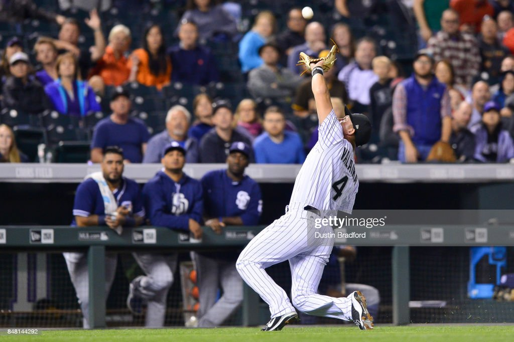 Pat Valaika #4 of the Colorado Rockies makes a sliding catch in foul ground to end the top of the eighth inning of a game against the San Diego Padres at Coors Field on September 16, 2017 in Denver, Colorado.