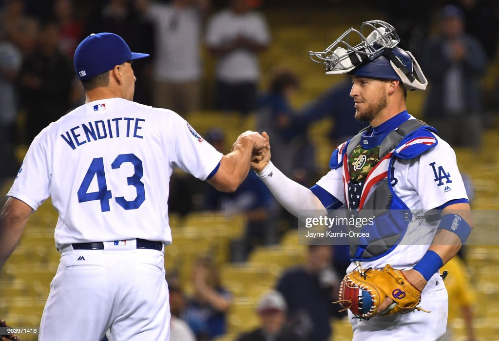 Pat Venditte #43 is met by Yasmani Grandal #9 of the Los Angeles Dodgers after earning a save in the ninth inning of the game against the Philadelphia Phillies at Dodger Stadium on May 30, 2018 in Los Angeles, California.