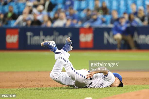 Pat Venditte lands on his face after tossing the ball to first after getting hit by a come backer as the Toronto Blue Jays play the Tampa Bay Rays at...