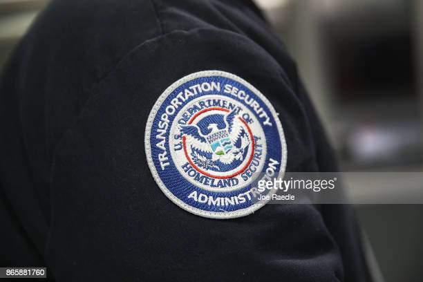 A patch is seen on the jacket of a Transportation Security Administration official as he works at the automated screening lanes funded by American...