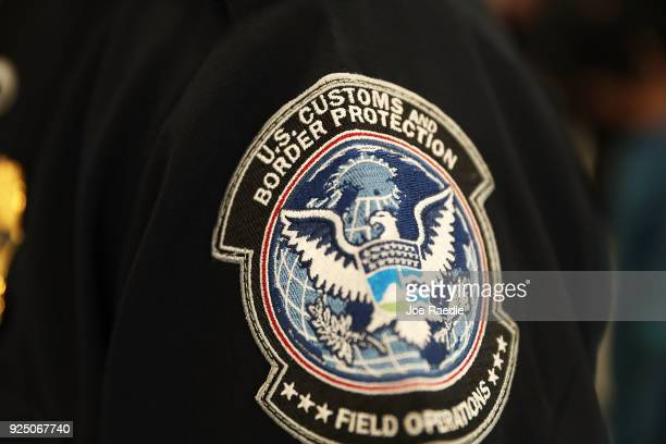 A patch is seen on the sleeve of a US Customs and Border Protection officer as he uses facial recognition technology in his booth at Miami...
