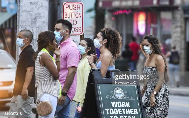 People wear masks while walking alongside the restaurants on Main Street in Patchogue, New York on July 11 during the coronavirus pandemic.