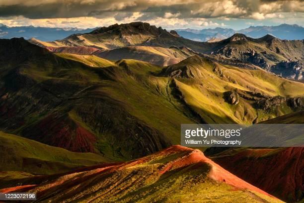 patchy sunlight casting light and shadows on the colorful rainbow mountain in cusco, peru - paisajes de peru fotografías e imágenes de stock