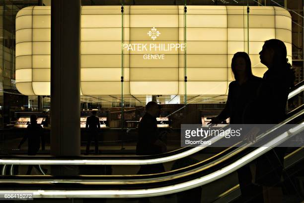 A Patek Philippe SA sign stands on display as visitors ride an escalator during the 2017 Baselworld luxury watch and jewellery fair in Basel...