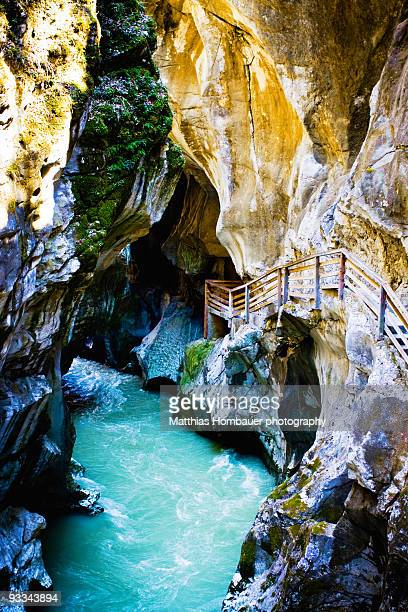 A path leading through a canyon with green water