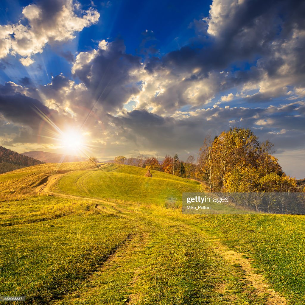 path on hillside meadow in mountain at sunset : Stock Photo