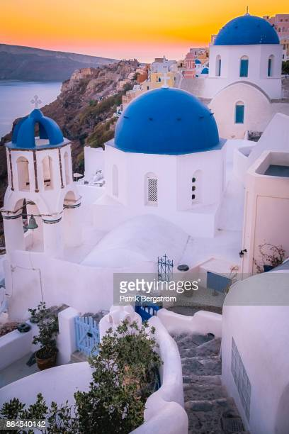 a path to blue dome church tops in santorini during sunset. - oia santorini foto e immagini stock
