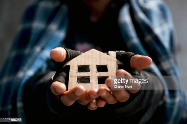 a pathetic homeless man begged the house on the sidewalk - sin techo fotografías e imágenes de stock