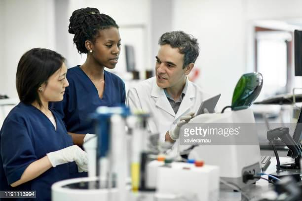 compañeros de trabajo de patología discutiendo datos en la tableta digital en el laboratorio - laboratorio clinico fotografías e imágenes de stock