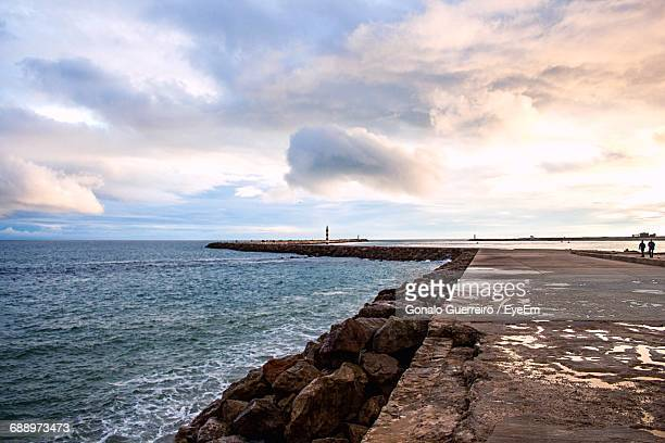 Pathway Along Sea Against Cloudy Sky