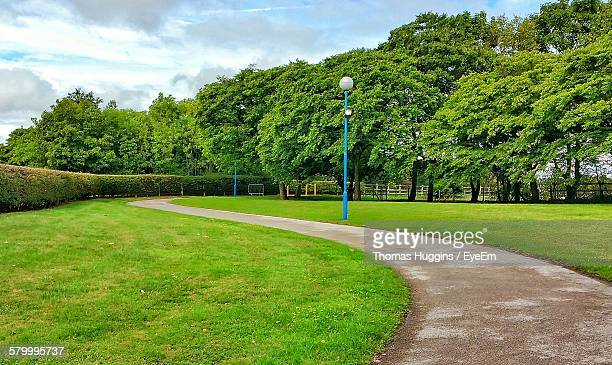 pathway by grassy field at park - pedestrian walkway stock pictures, royalty-free photos & images
