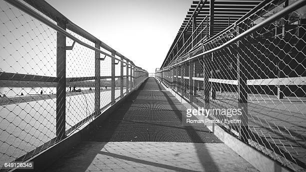 pathway by river against sky on sunny day - roman pretot stock-fotos und bilder