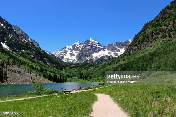 pathway leading towards lake by maroon bells mountains against clear sky - maroon bells stock pictures, royalty-free photos & images