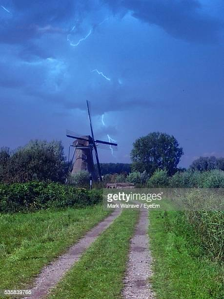Pathway Leading Towards Windmill Against Storm Clouds