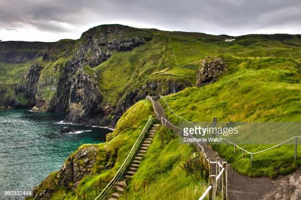 pathway to carrick-a-rede in county antrim, northern ireland. - islas de gran bretaña fotografías e imágenes de stock