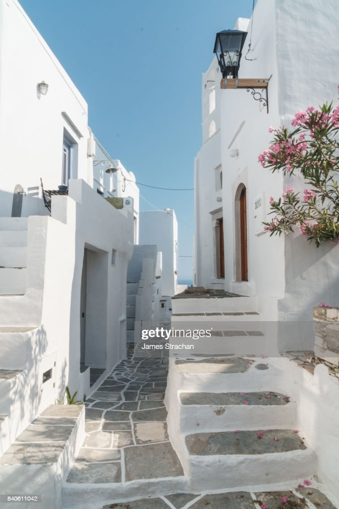 Pathway winds through traditional white Greek houses, framed by old street  light and flowers,