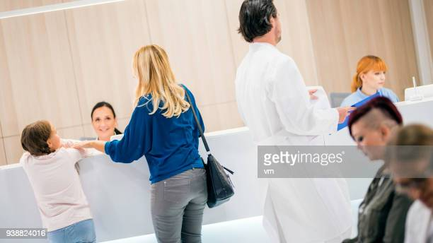 patiens in waiting room - medical building stock photos and pictures