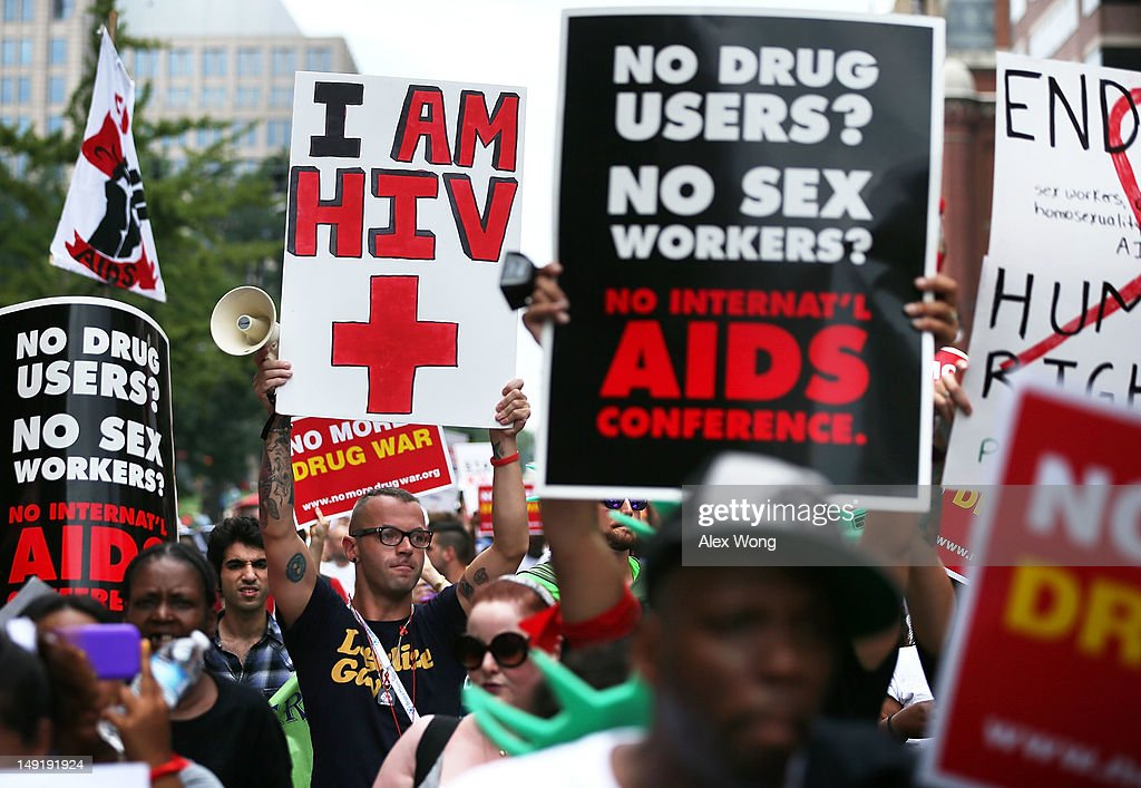 HIV+ patient Aaron Laxton (Center R) of St. Louis, Missouri, and other activists participate in a march from the Washington Convention Center to the White House July 24, 2012 in Washington, DC. AIDS activists from organizations all around the world participated in the march to 'demand rights and resources to confront and cure HIV/AIDS.'