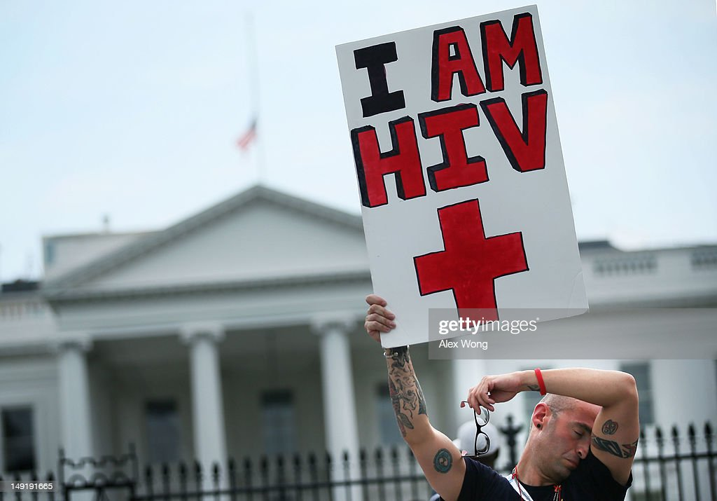 HIV+ patient Aaron Laxton of St. Louis, Missouri, holds up a sign in front of the White House after a march from the Washington Convention Center July 24, 2012 in Washington, DC. AIDS activists from organizations all around the world participated in the march to 'demand rights and resources to confront and cure HIV/AIDS.'