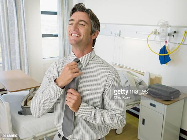 Patient adjusting necktie in hospital room