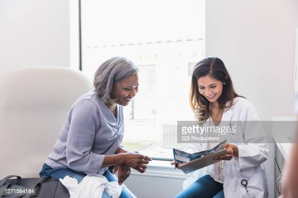 patient and doctor discussing healthcare options - pamphlet stock pictures, royalty-free photos & images