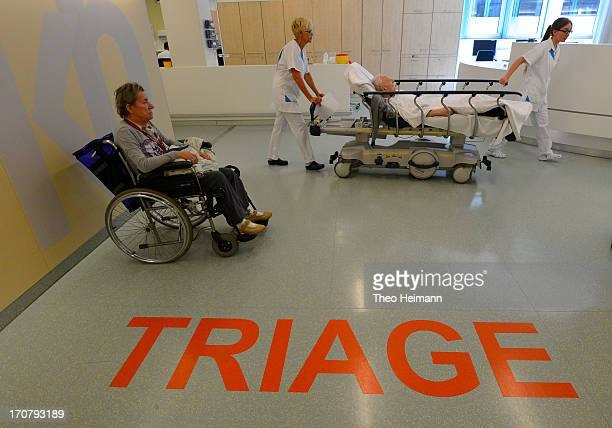 A patient and health care professionals walk through the triage department at the Unfallkrankenhaus Berlin hospital in Marzahn district on June 17...