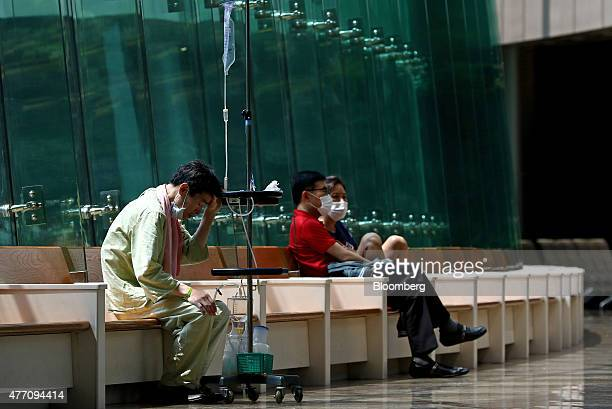 A patient and people wearing masks sit inside the Samsung Medical Center in Seoul South Korea on Sunday June 14 2015 South Korea reported seven...