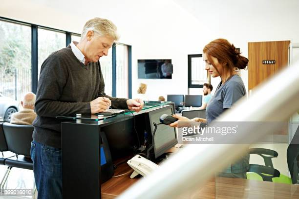 Patient at dentist paying for dental treatment