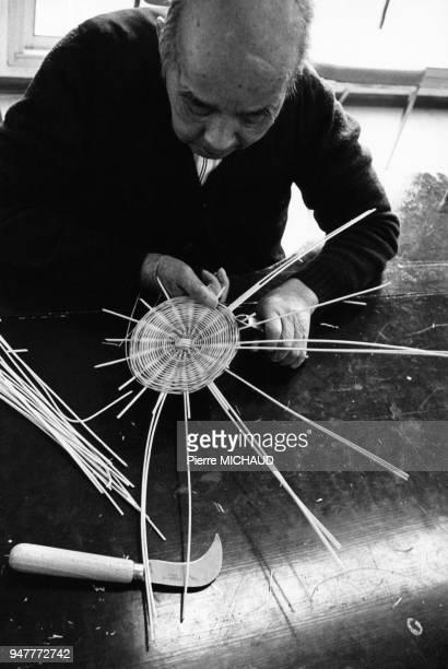 Patient fabricant un panier dans le cadre d'une scéance de rééducation d'ergothérapie par la vannerie en 1986 France