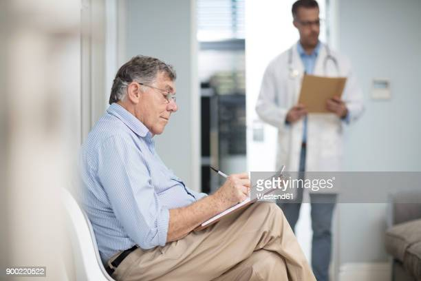 patient filling in file in medical practice - form filling stock photos and pictures