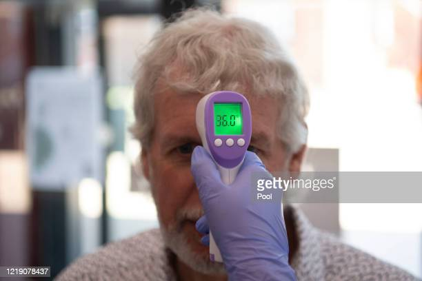 Patient has his temperature taken with a non-contact infrared thermometer on arrival at Freshney Green Primary Care Centre on June 9, 2020 in...