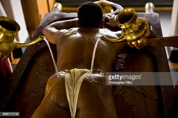 A patient has warm water poured over his body after having completed a massage with medicated oil as part of the overall Ayurveda experience at...