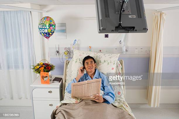 Patient holding a newspaper and talking on a mobile phone in a hospital room