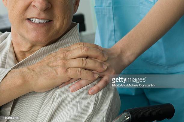 patient holding nurse's hand, cropped - hand on shoulder stock photos and pictures