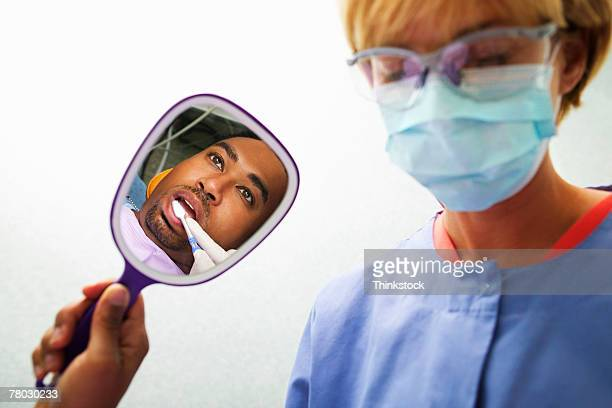 A patient holds a mirror to see what the hygienist is doing during a dental exam