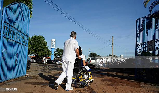 A patient in a wheelchair arrives at the 'Casa de Dom Inacio de Loyola' in Abadiania 120km southwest of Brasilia state of Goias on April 4 2012...