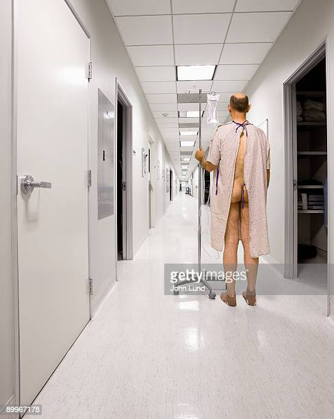 Patient in gown standing in long hospital hallway.