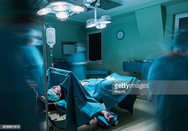 Patient in operating room with doctors in blurred motion.