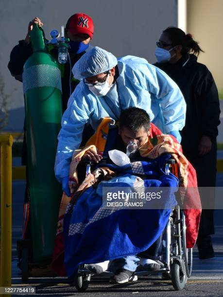A patient infected with COVID19 is helped by a nurse outside the regional Honorio Delgado Hospital in the Andean city of Arequipa south of Peru on...