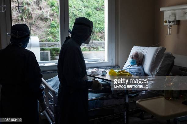 Patient infected with Covid-19 reacts after she received a Colomba traditional Easter cake handed by a nurse on April 4, 2021 at the Covid ward of...