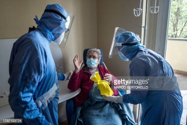 Patient infected with Covid-19 reacts as she receives a Colomba traditional Easter cake handed by a nurse on April 4, 2021 at the Covid ward of the...
