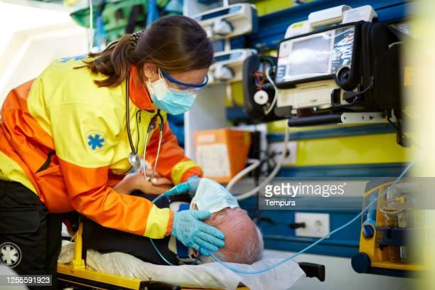 救急車の中の患者で、保護マスクを着用しています。 - 救急救命士 ストックフォトと画像