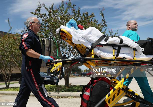 A patient is evacuated from the Baptist Hospitals of Southeast Texas building after it was closed when water to the building was cut off after...