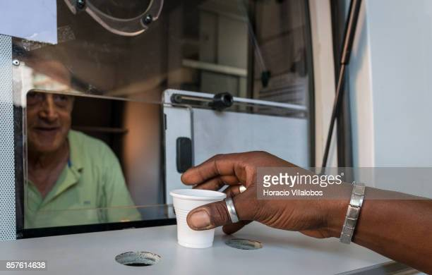 A patient is handed his daily dose of 85 milligrams of methadone by male nurse Joao Matos from a van parked near Praca Espanha on October 04 2017 in...